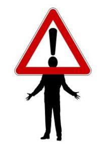 Mensch in schwarz-weiß gezeichnet. Sein Kopf ist der Punkt einen Ausrufezeichens, das von einem Warndreieck umschlossen ist – als Ausdruck für Angst als Signal