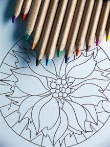 Buntstifte in verschiedenen Farben liegen auf einem Blütenmandala und laden zum Ausmalen ein