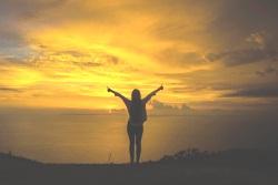 Eine Frau steht am Rand eines Berggipfels. Sie hat die Arme über ihren Kopf weit ausgebreitet, ihre Zeigefinger sind ausgestreckt – sie hat es geschafft. Vor ihr liegt Weite und der Himmel erstrahlt im gelben Licht des Sonnenaufgangs