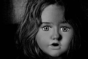 Frau mit aus Angst weit aufgerissenen Augen und offenen Mund. Das Gesicht wirkt wie das einer Puppe oder einer Maske