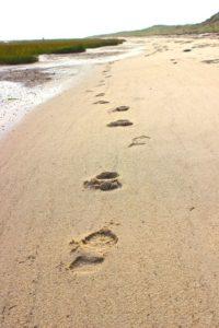 """Fußspuren im Sand als Weg """"raus aus dem Stress"""""""