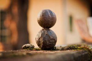 Zwei Kugeln aus Stein stehen übereinander – in Harmonie zu sich sein durch Autogenes Training
