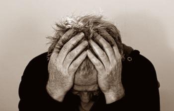 Foto in schwarz-weiß: Ein Mann hält seine Hände an den Kopf. Er hat Schmerzen