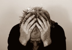 Foto in sepia: Ein Mann hält seine Hände an den Kopf. Er hat Schmerzen
