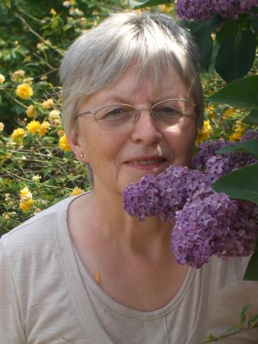 Portraitfoto Sigrid Schenk-Ulbrich ihrem Garten. Ich rieche so gern Flieder, der am rechten unteren Rand zu sehen ist.