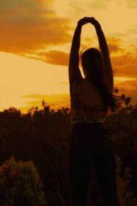 Eine Frau streckt sich dem Morgenrot mit ausgestreckten Armen entgegen; sie hat es geschafft – ihren Stress überwunden